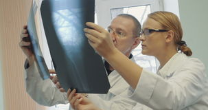 Doctors analyzing the results of x-ray examination stock video
