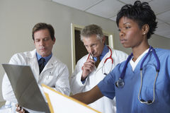 Doctors Analyzing X-Ray Report Stock Photography