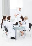 Doctors answering colleague in meeting Stock Images