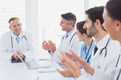Doctors applauding a fellow doctor Stock Photos