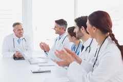 Doctors applauding a fellow doctor Royalty Free Stock Photography