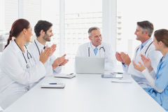 Doctors applauding a fellow doctor Royalty Free Stock Images