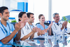 Doctors applauding while sitting at a table Royalty Free Stock Photos