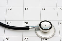 Doctors Appointment. A stethoscope sitting on a calendar background, doctors appointment stock image