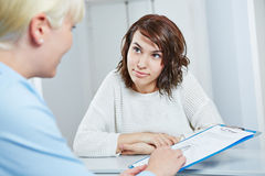 Doctors assistant giving form to patient Stock Photography