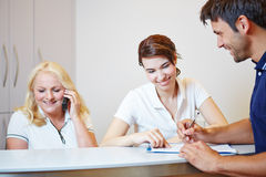 Doctors assistant helping patient to fill out form Stock Photos