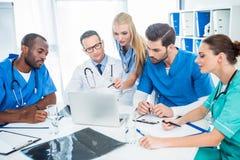 Doctors brainstorming. Multiethnic team of doctors brainstorming and using laptop Stock Photo