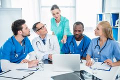 Doctors brainstorming and using laptop. Concentrated multiethnic team of doctors brainstorming and using laptop Royalty Free Stock Images