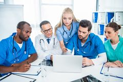 Doctors brainstorming and using laptop. Focused multiethnic team of doctors brainstorming and using laptop Royalty Free Stock Photo
