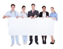 Doctors and businesspeople with billboard. Happy Doctors And Businesspeople Holding White Billboard Over White Background Royalty Free Stock Images