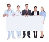 Doctors and businesspeople with billboard. Happy Doctors And Businesspeople Holding White Billboard Over White Background Stock Photo