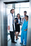 Doctors and businesswoman standing in elevator Royalty Free Stock Image
