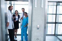 Doctors and businesswoman standing in elevator. In hospital stock photos