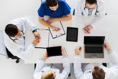 Doctors with cardiogram and computers at hospital Royalty Free Stock Images