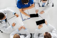 Doctors with cardiograms and tablet pc at hospital Stock Images