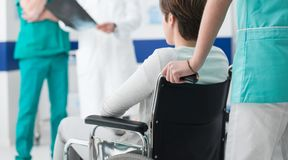Doctors checking a disabled patient`s x-ray royalty free stock image
