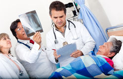 Doctors checking on an elder patient Stock Photo