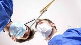 Doctors checking over a patient. Low angle view. POV view from the patient perspective. The surgeons are looking down stock footage