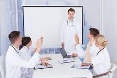 Doctors clapping for colleague after presentation in hospital Royalty Free Stock Photo