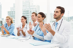 Doctors clapping hands in meeting Stock Image