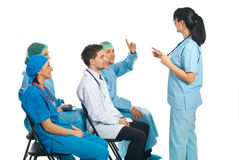 Doctors conference. Doctor woman pointing to a surgeon man with hand raised who know the answer to question at conference Royalty Free Stock Image