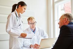 Doctors in consultation with patient. About advice for therapy Royalty Free Stock Image