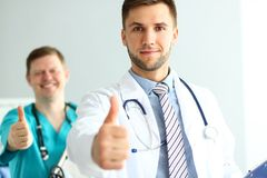 Doctors demonstrating approval sign. Portrait of joyful colleagues showing ok gesture and looking at camera. Happy men with thumbs-up in act of admiration. Doc royalty free stock images