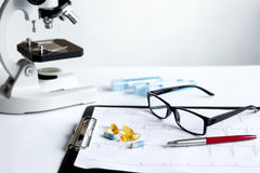 Doctors desk with microscope and test tubes Royalty Free Stock Images
