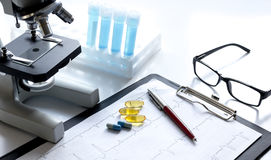 Doctors desk with microscope and test tubes Royalty Free Stock Photography