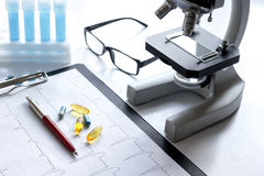 Doctors desk with microscope and test tubes Stock Image