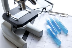 Doctors desk with microscope and test tubes Stock Photos