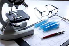 Doctors desk with microscope and test tubes Stock Images
