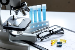 Doctors desk with microscope and test tubes Stock Photography