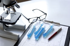 Doctors desk with microscope and test tubes Royalty Free Stock Photos