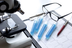 Doctors desk with microscope and test tubes Stock Photo