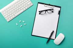 Doctors desk with tablet, pen, keyboard, mouse and pills royalty free stock photos