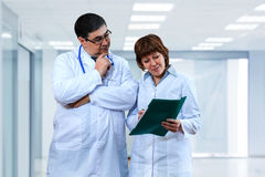 Doctors discuss the diagnosis. A doctor and a nurse are talking at the clinic. Medical institution royalty free stock photos