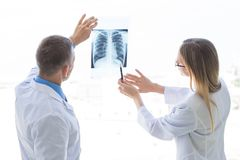 Doctors discuss x-ray. Doctors look and discuss x-ray in a clinic or hospital stock images