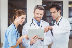 Doctors discussing while holding digital tablet Royalty Free Stock Photos