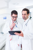 Doctors discussing images of x-ray scan in CT. Doctors discussing images of x-ray scan standing in front of CT machine in hospital Royalty Free Stock Photo