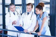 Doctors discussing medical report in corridor. Doctors discussing medical report in hospital corridor Royalty Free Stock Photo