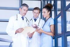 Doctors discussing medical report in corridor. Doctors discussing medical report in hospital corridor Stock Image