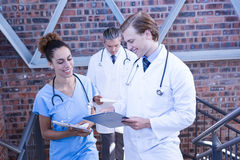 Doctors discussing medical report on staircase. In hospital Stock Photo