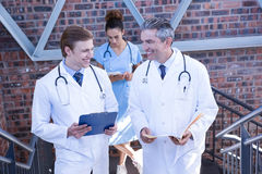 Doctors discussing medical report on staircase. In hospital Royalty Free Stock Photography