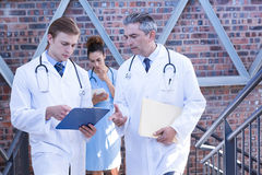Doctors discussing medical report on staircase. In hospital Royalty Free Stock Images