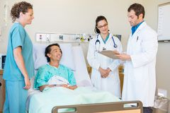 Doctors Discussing Notes While Nurse And Patient Stock Photography