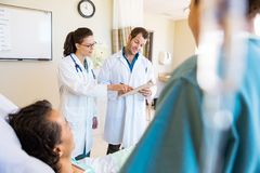 Doctors Discussing Notes With Patient And Nurse In Royalty Free Stock Photo