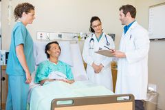 Doctors Discussing Notes While Patient And Nurse Stock Photo