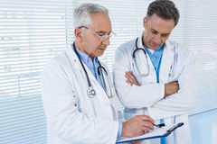 Doctors discussing over clipboard Stock Photo