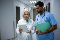 Doctors discussing over digital tablet in corridor Royalty Free Stock Photos